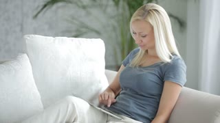 Charming young woman sitting on sofa using touchpad holding apple and smiling