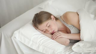 Charming young woman sleeping in bed moving and smiling in her sleep