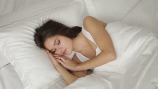 Charming young woman sleeping in bed waking up looking at camera and smiling