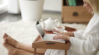 Charming young woman wearing bathrobe sitting on floor using laptop and smiling. Panning camera