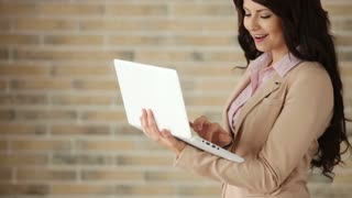 Cheerful businesswoman using laptop and smiling at camera
