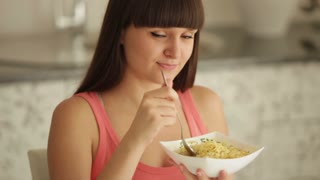 Cheerful girl at kitchen eating noodle and smiling