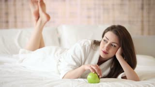 Cheerful girl lying on bed holding green apple looking at camera and smiling
