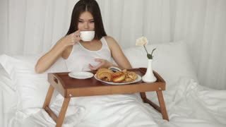 Cheerful girl relaxing in bed drinking from cup looking at camera and smiling. Panning camera