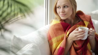 Cheerful girl relaxing on sofa by window drinking tea looking at camera and smiling. Panning camera