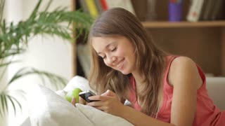 Cheerful girl relaxing on sofa using mobile phone eating apple looking at camera and smiling
