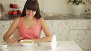 Cheerful girl sitting at kitchen table and eating noodle