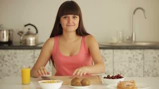 Cheerful girl sitting at kitchen table and peeling kiwi fruit