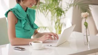 Cheerful girl sitting at office desk with cup of coffee using laptop looking at camera and smiling. Panning camera