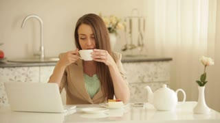 Cheerful girl sitting at table drinking tea using laptop and smiling