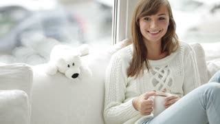Cheerful girl sitting by window drinking tea looking at camera and smiling. Panning camera