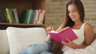 Cheerful girl sitting on sofa reading book and smiling