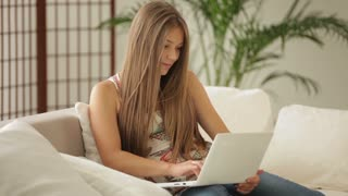 Cheerful girl sitting on sofa using laptop and smiling at camera
