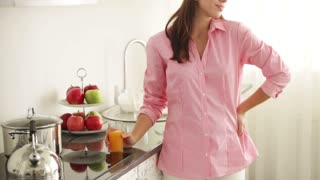 Cheerful girl standing in kitchen drinking juice looking at camera and smiling. Panning camera