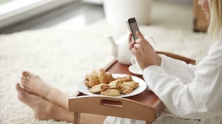 Cheerful girl wearing bathrobe sitting on floor with tray of food using mobile phone looking at camera and smiling. Panning camera