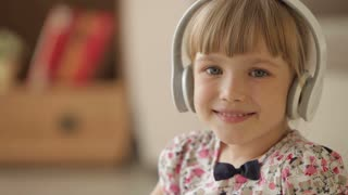 Cheerful little girl in headset smiling and laughing at camera
