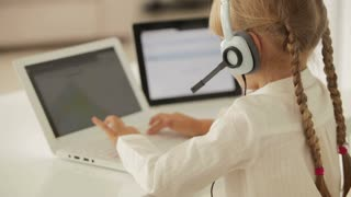 Cheerful little girl in headset with microphone sitting at table using laptop and smiling at camera