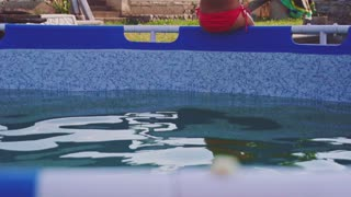 Cheerful little girl is having fun in the outdoors swimming pool. Slow Motion 240 fps. Child is jumping and playing in the water, on a warm summer day. Happy childhood concept.