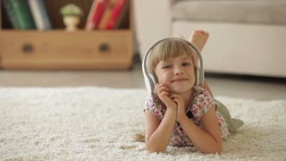 Cheerful little girl lying on carpet in living room listening to music on headphones and smiling at camera