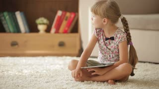 Cheerful little girl sitting on floor using touchpad and smiling at camera
