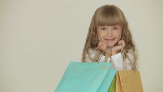 Cheerful pretty little girl posing with multicolored paper bags