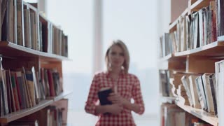 Cheerful young lady in library coming and looking at camera