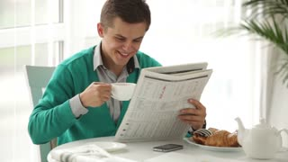 Cheerful young man sitting at table reading newspaper drinking tea and smiling. Panning camera