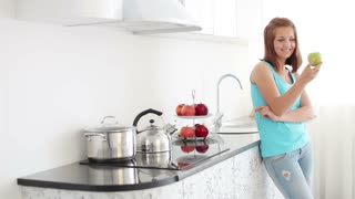 Cheerful young woman in kitchen holding apple and smiling