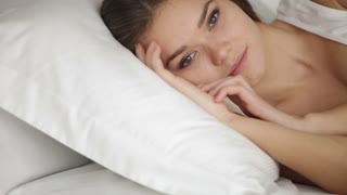 Cheerful young woman lying in bed looking at camera and smiling. Panning camera