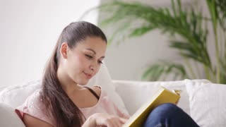 Cheerful young woman reading book holding it to her chest and smiling