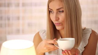 Cheerful young woman sitting at cafe drinking tea and smiling at camera. Panning camera