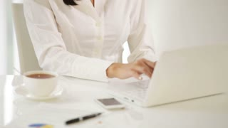Cheerful young woman sitting at office desk using laptop looking at camera and smiling. Panning camera