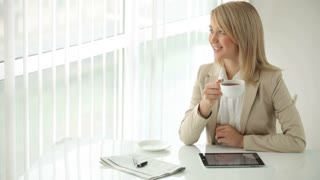Cheerful young woman sitting at office table drinking coffee and smiling