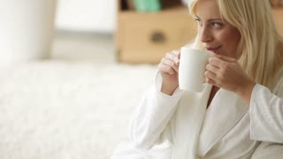 Cheerful young woman wearing bathrobe sitting on floor drinking from cup looking at camera and smiling. Panning camera