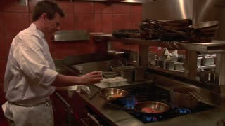 Chef Cooks At Stove With Flaming Frying Pan