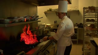 Chef With Flaming Frying Pan On Stove