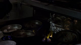 Chefs Cooking Over Flame in Kitchen