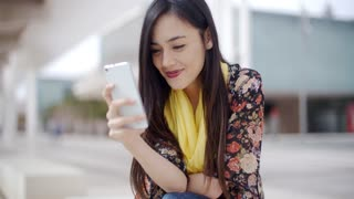 Chic young woman reading a mobile message