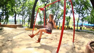 Child and his mother ride on a swing. Camera flies