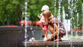 Child and mother in the fountains. Mother takes baby shoes