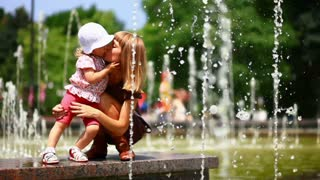 child and mother in the fountains. They play with water