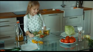Child chef prepared a salad. Child tasting salad tastes. Delicious. Thumbs up. Ok. Zooming