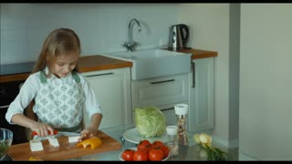 Child cutting feta cheese and putting cheese in bowl. Child chef in the kitchen looking at camera and smiling. Zooming