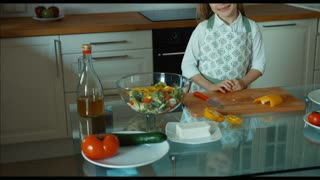 Child cutting feta cheese. Child chef in the kitchen looking at camera and smiling. Zooming