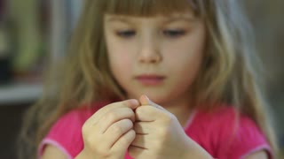 Child develops motor skills finger. Girl making jewelry from beads. Closeup