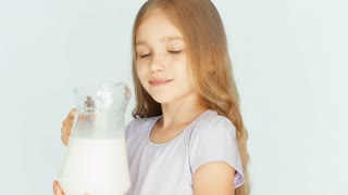 Child drinking milk from jug on a white background. Thumb up. Ok. Closeup. Milk mustache. Big eyes