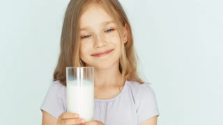 Child drinking milk. Girl showing glass of milk at camera. Girl with beautiful blond hair on a white background. Big eyes. Closeup