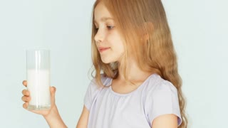 Child drinking milk. Milk mustache. Girl with beautiful blond hair on a white background. Thumb up. Ok. Closeup