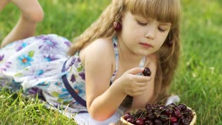 Child eating cherries lying on the grass