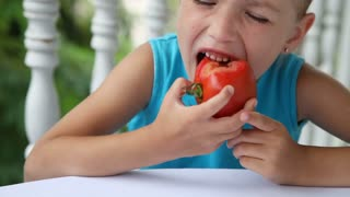 Child eating tomato. Close-up portrait. Girl looking at camera and smiling